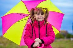 Rolig gullig flicka med det färgrika paraplyet som spelar i trädgården royaltyfri foto