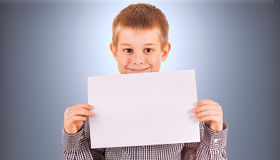 Rolig gullig pojke med det vita arket av papper Royaltyfri Fotografi