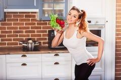 Rolig idrotts- kvinna som rymmer den glass bunken med olika grönsaker som ler nära framsidan Royaltyfri Fotografi