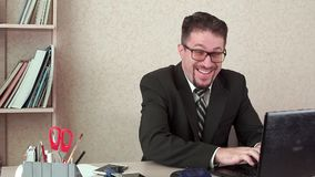 Rolig kontorschef, roligt skriva meddelande i bärbar dator Han är i arbetsplatsen lager videofilmer