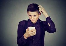 Rolig korkad dum grabb som har problem med hans smartphone Fotografering för Bildbyråer