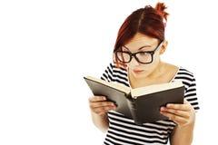 Rolig kvinna i stora exponeringsglas med en bok arkivbilder