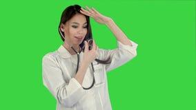 Rolig kvinnlig doktor som spelar med en stetoskop på en grön skärm, Chromatangent arkivfilmer