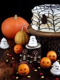 Rolig läcker sammansättning för allhelgonaafton med kakan, kex, marshmallowen och mandariner på tabellen Sötsaker i form av spöke Arkivfoto
