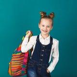 Rolig le liten flicka med den stora ryggsäcken som hoppar och har f Royaltyfri Bild