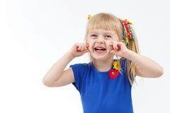 Rolig liten blond flicka med två svansar som gör grimasen arkivfoton