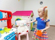 Rolig liten blond flicka som matar hennes vännallebjörn royaltyfria foton