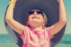 Rolig liten flicka i en stor randig hatt på stranden Fotografering för Bildbyråer