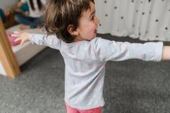 Rolig liten flicka i gulliga pijamas som har gyckel royaltyfria foton
