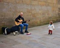 Rolig liten flicka och man som nästan spelar gitarren i en domkyrka för gata Santiago de Compostela Spanien, 22 Februari 2019 arkivfoton