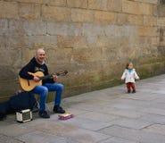 Rolig liten flicka och man som nästan spelar gitarren i en domkyrka för gata Santiago de Compostela Spanien, 22 Februari 2019 royaltyfria foton