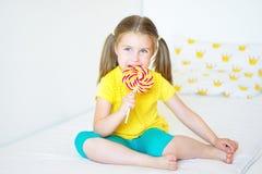Rolig liten flicka som äter den stora sockerklubban Fotografering för Bildbyråer