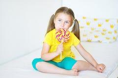 Rolig liten flicka som äter den stora sockerklubban Arkivbild