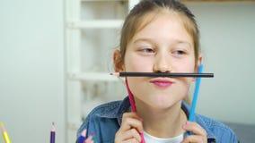 Rolig liten flicka som gör framsidor med kulöra blyertspennor som mustasch stock video