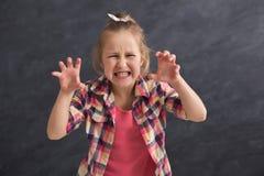 Rolig liten flicka som imiterar den ilskna tigern på mörk bakgrund Arkivbilder