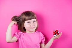 Rolig liten flicka som rymmer den nätta prickiga gåvaasken i hennes händer på ljus rosa bakgrund Arkivbild