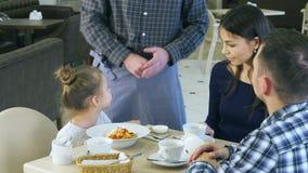 Rolig liten flicka som spelar med hennes leksak, innan att äta hennes matställe i kafé med henne föräldrar Uppassaren kommer med  stock video