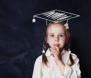 Rolig liten flicka som tänker och väljer favorit- kurs royaltyfri foto