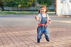 Rolig liten flickabanhoppning för glädje ett ungt barn i grov bomullstvilloveraller royaltyfri bild
