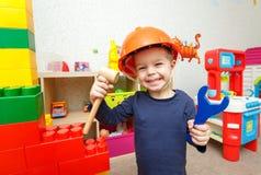 Rolig liten repairman med den leksakhammaren och skiftnyckeln royaltyfri fotografi