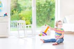Rolig litet barnflicka med pyramidleksaken i vitt rum arkivfoton