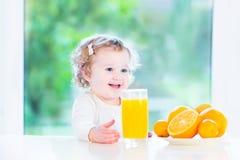 Rolig lockig litet barnflicka som dricker orange fruktsaft royaltyfri foto