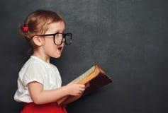 Rolig lycklig flickaskolflicka med boken från svart tavla Royaltyfri Foto