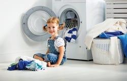 Rolig lycklig liten flicka för barn som tvättar kläder i tvättstuga arkivfoto