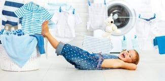 Rolig lycklig liten flicka för barn som tvättar kläder och skratt i laund arkivfoton