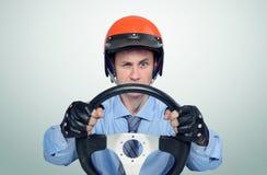 Rolig man i en röd hjälm med styrninghjulet, begrepp för bilchaufför royaltyfri bild