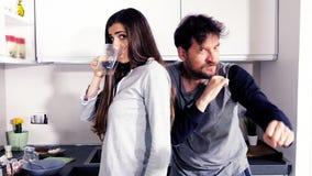 Rolig man och kvinna i pyjamas i kök som ser kameran som dricker att dansa för kaffe som är lyckligt stock video