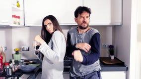 Rolig man och kvinna i pyjamas i kök som ser kameran som dricker att dansa för kaffe som är lyckligt lager videofilmer