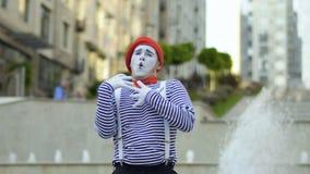 Rolig manfars i röd basker och avriven skjorta som sjunger på springbrunnbakgrund lager videofilmer