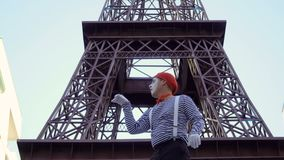 Rolig manfars i röd basker och avrivna skjortan som spelar nära Eiffeltorn stock video