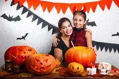 Rolig moder och dotter som har gyckel hemma Lycklig familj som förbereder sig för allhelgonaafton Bärande karnevaldräkter för fol fotografering för bildbyråer