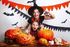 Rolig moder och dotter som har gyckel hemma Lycklig familj som förbereder sig för allhelgonaafton Bärande karnevaldräkter för fol royaltyfri fotografi