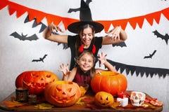 Rolig moder och dotter som har gyckel hemma Lycklig familj som förbereder sig för allhelgonaafton Bärande karnevaldräkter för fol royaltyfria bilder