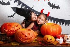 Rolig moder och dotter som har gyckel hemma Lycklig familj som förbereder sig för allhelgonaafton Bärande karnevaldräkter för fol arkivbilder