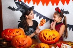 Rolig moder och dotter som har gyckel hemma Lycklig familj som förbereder sig för allhelgonaafton Bärande karnevaldräkter för fol royaltyfri foto