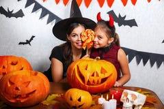 Rolig moder och dotter som har gyckel hemma Lycklig familj som förbereder sig för allhelgonaafton Bärande karnevaldräkter för fol arkivfoton