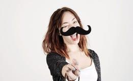 Rolig moderiktig modeflicka med den pappers- mustaschen som spelar med sinnesrörelse Fotografering för Bildbyråer