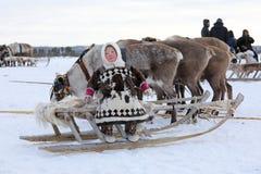 Rolig Nenets flicka i pälskläder med en nationell prydnad på bet Arkivbild