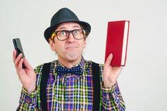 Rolig nerd med exponeringsglas med boken och mobiltelefonen Skämtsam man i rutig skjorta och svart hatt Upphetsad man som har en  royaltyfria bilder