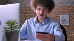 Rolig nerdy affärsman med shopping för lockigt hår till och med internet på bärbara datorn och betala med kreditkorten som in sit stock video