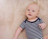 Rolig nyfödd pojke som bär i avrivna kläder Royaltyfri Foto