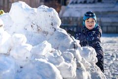 Rolig pojke för liten unge i färgrik kläder som utomhus spelar under snöfall Aktiv fritid med barn i vinter på kall snöig da Arkivbilder