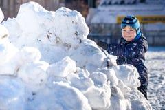 Rolig pojke för liten unge i färgrik kläder som utomhus spelar under snöfall Aktiv fritid med barn i vinter på kall snöig da Royaltyfri Foto