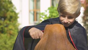 Rolig pojke i vampyrdräkt som snider stålar-nolla-lyktan, allhelgonaaftonhelgdagsaftonförberedelser lager videofilmer