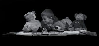 Rolig pojke med välfyllda djur som läser en bok för sängtid ar Royaltyfri Foto