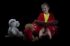 Rolig pojke med välfyllda djur som läser en bok för sängtid ar Arkivfoto